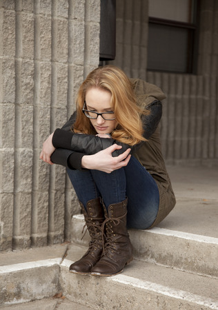 Outdoor photo of young teenage girl seated on concrete steps, hugging knees, distraught facial expression  版權商用圖片