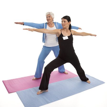 Female yoga instructor teaching  Warrior  position to senior adult woman on white background