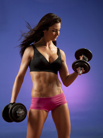 Studio photo of attractive young woman lifting dumbbells 版權商用圖片