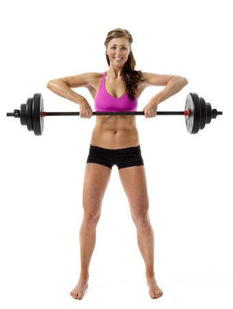 Full length front view of attractive young woman lifting barbell on white background. photo
