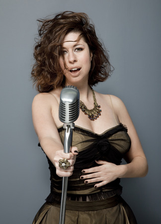 Front view studio photo of attractive young adult singer with microphone on gray background.