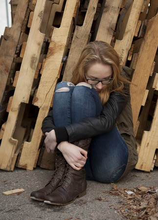 Outdoor photo of young teenage girl seated on ground, hugging knees, looking down at ground.