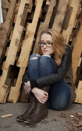 hugging knees: Outdoor photo of young teenage girl seated on ground, hugging knees, distaught facial expression. Stock Photo