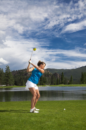 Outdoor photo of attractive woman golfing