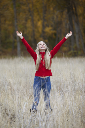 Outdoor photo of pretty young girl standing in field, arms extended upward 版權商用圖片