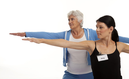 Yoga instructor coaching senior woman on white background 版權商用圖片