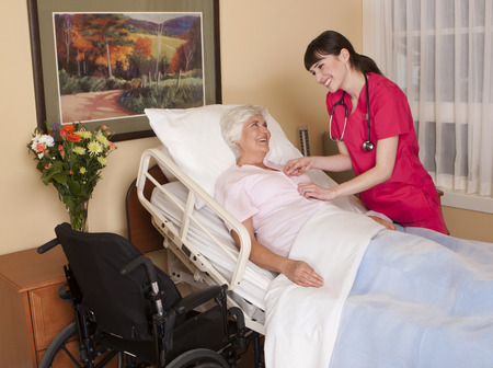 private room: Nurse interacting with mature female patient in private health care setting.
