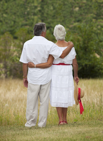 facing away: Outdoor photo of mature couple standing, facing away from camera.