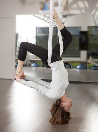 Photo of woman doing aerial yoga pose.