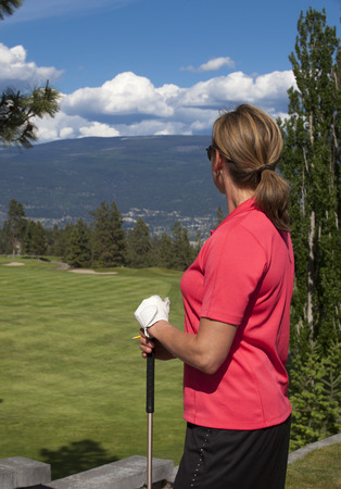 facing away: Outdoor photo of female golfer looking at golf course, facing away from camera.