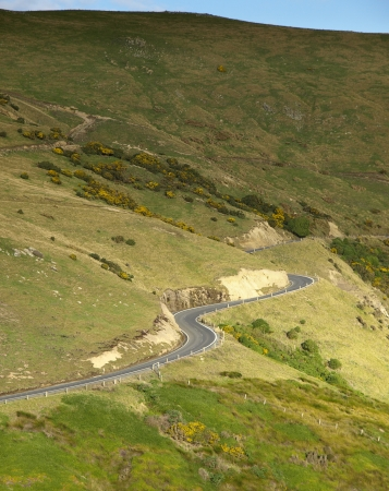 The road with curve goes to the mountain near Dunedin, New Zealand photo