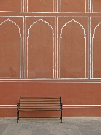 The vintage bench for tired tourists behind the wall of Jaipur City Palace, India photo