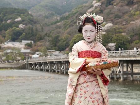 Maiko at togetsukyo bridge in kyoto, japan