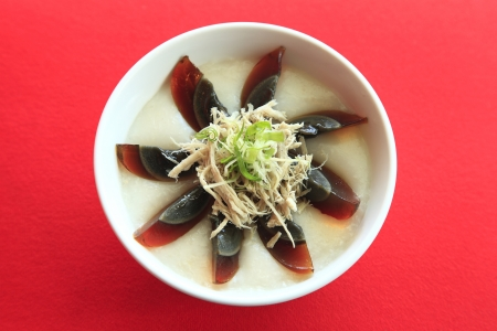 a bowl of rice porridge with chicken and potash preserved egg photo