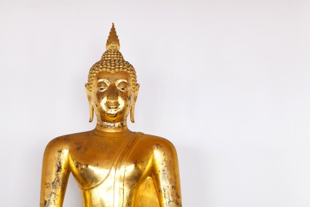 Buddha statue made of stucco and covered with lacquer and gold leaves have been placed in front of the grey wall. Stock Photo - 14300561