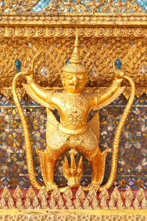 dazzlingly: The statue of Garuda battling naga serpent on the wall of temple in Thailand