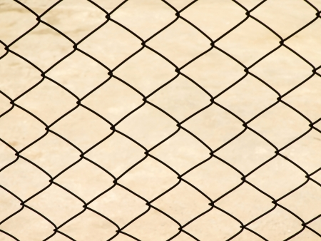 Metal net with ground on background photo