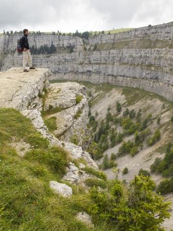 jura: CREUX DU VAN, NEUCHATEL, SWITZERLAND - SEP 9: An unidentified hiker look at the natural rocky cirque of Creux du Van on September 9, 2010 in Neuchatel, Switzerland.