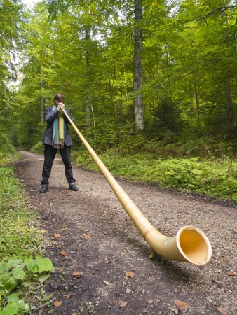 cor: NEUCHATEL, SWITZERLAND - SEPTEMBER 18: Swiss musician playing his typical Alphorn for a group of hikers while hiking to the summit of Creux du Van on September 18, 2010 in Neuchatel, Switzerland