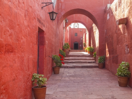 medioeval: Red painted walls and arches design of alleyway through the Santa Catalina Monastery in Arequipa, Peru  Editorial