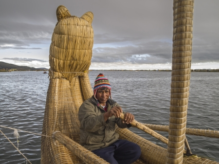 PUNO, PERU - MAR 13  Peruvian rows Totora Reed boat on Mar 13, 2011 in Lake Titicaca, Puno, Peru  These reeds have been used by various pre-Columbian South American civilizations to build reed boats