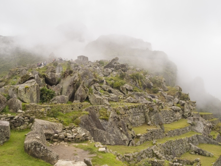 messily: Scattered stones in the ruins site of a pre-Columbian 15th-century Inca site of Machu Picchu after rain in Machupicchu District, Urubamba Province, Cusco Region, Peru