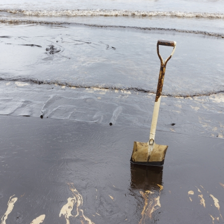 A Spade on dirty beach as tool to scoop crude oil on clean-up operation from crude oil spilled into Ao Prao Beach on July 31, 2013 in Rayong province, Thailand  Archivio Fotografico