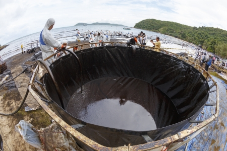 RAYONG, THAILAND - JULY 31, 2013  Workers in biohazard suits pouring spilled crude oil into big tank as cleaning operations from a beach of Samet Island on July 31, 2013 in Rayong, Thailand