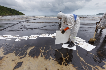 Rayong, Thailand - July 31, 2013  A Worker in biohazard suit placing absorbent paper in a clean-up operation of crude oil spilled at Ao Prao Beach on July 31, 2013 in Koh Samet, Rayong, Thailand  Editoriali