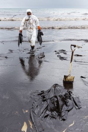RAYONG, THAILAND - JULY 31, 2013  A worker in biohazard suit during the clean-up operation from crude oil spilled into Ao Prao Beach on July 31, 2013 in Rayong province, Thailand
