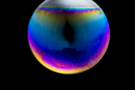 Close up of a colorful Soap Bubble over black background look like strange planet in universe  photo