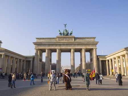 winning location: BERLIN, GERMANY - NOV 12: Unidentified young men dress as a bear, Russian and german soldiers stand as a tourist attraction in front the Brandenburg gate on November 12, 2011 in Berlin, Germany.