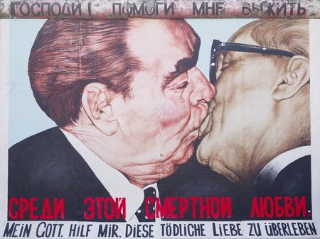 BERLIN - NOV 12: Graffiti Kiss between Brezhnev and Honecker by Dm.Vrubel on Berlin Wall at East Side Gallery on November 12, 2011 in Berlin, Germany. Editoriali