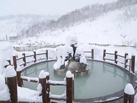 Open air Japanese public bath pool on snowy day in winter, Hokkaido, Japan.