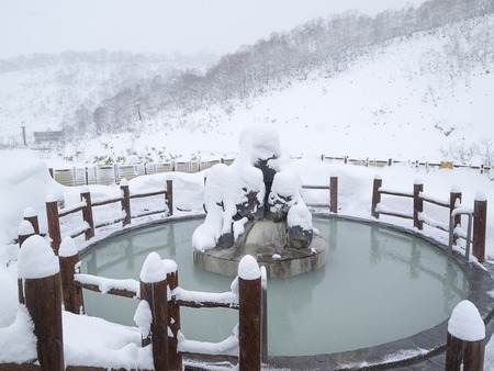 Open air Japanese public bath pool on snowy day in winter, Hokkaido, Japan.