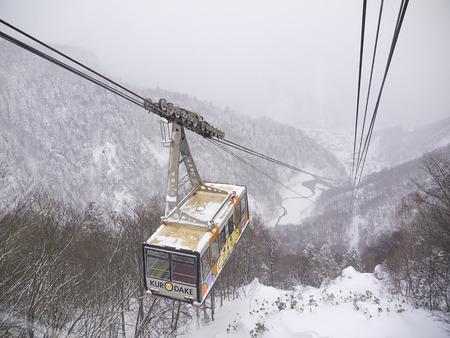 HOKKAIDO, JAPAN - DEC 16: Kurodake ropeway car ascending to the 5th Station halfway up to the summit of Mount Kurodake that towers over Sounkyo Onsen on Dec 16, 2011 in Central Hokkaido, Japan.