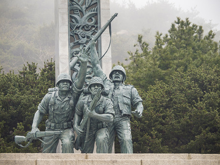 upholding: INCHEON, SOUTH KOREA-MAR 30: The statue of three soldiers in front of the statue of upholding liberty in Incheon Landing Operation Memorial Hall on Mar 30, 2012 in Incheon, South Korea.
