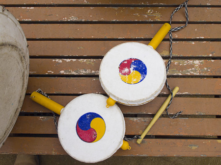 Old Traditional Korean handy drums on old painted wooden floor. Archivio Fotografico