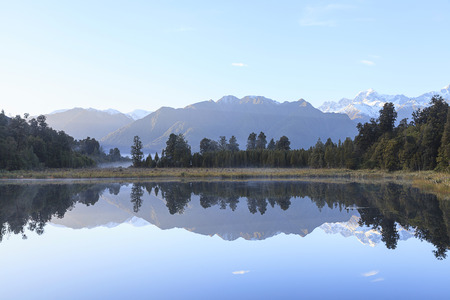 Reflection of Lake Matheson with Mount Cook and Mount Tasman as background, West Coast region, South Island, New Zealand. photo