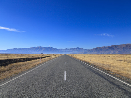 new horizon: Straight empty Country Road leading to Mountains lining the horizon on sunny day, Otago region, South Island, New Zealand.