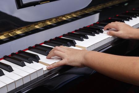 Boys hands play on piano keys.