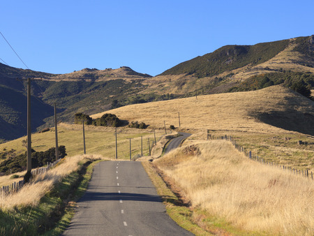 canterbury: Colorful countryside of tussock and mountains on the way to Akaroa, Canterbury region, South Island, New Zealand. Stock Photo
