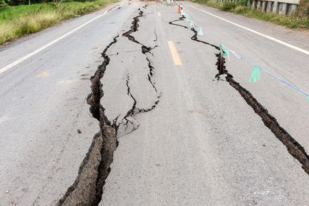 Asfaltweg gekraakt en gebroken van de aardbeving. Stockfoto