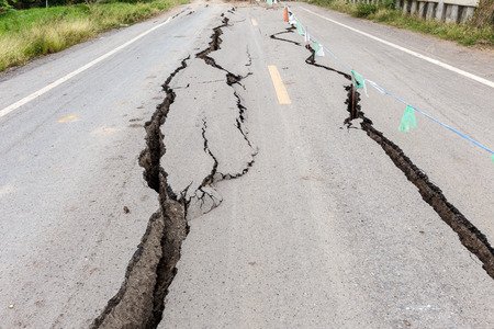 road construction: Asphalt road cracked and broken from earthquake. Stock Photo