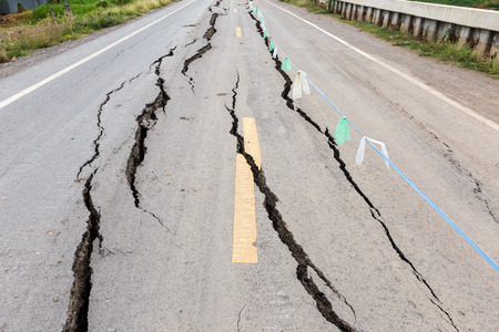 Asphalt road cracked and broken from earthquake. Archivio Fotografico