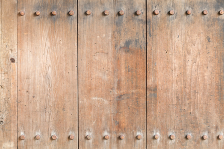 Weathered aged wooden board texture with iron rivets, bolts. (For use as a background)