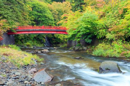 Red bridge and Fudo waterfall at Mount Nakano-Momiji, Kuroishi city, Aomori prefecture, Tohoku region, Japan. Mt.Nakano Momijiyama is designated as one of the 100 Autumn leaves spots in Japan