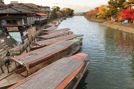 gondoliers: KYOTO, JAPAN -NOV 24, 2012: Gondoliers prep boats for cruises on the Uji River in city of Uji, Kyoto, Japan. River cruises and cormorant fishing are popular summer activities aimed at tourists in Uji. Editorial