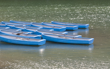 Group of blue rowboats moored on Katsura river with shower rain in Arashiyama area, Kyoto, Japan.