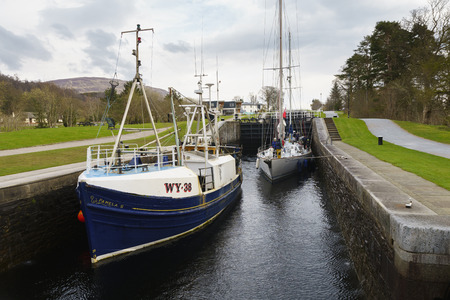 FORT WILLIAM, SCOTLAND - APR 12, 2016:: Boat at Neptunes Staircase lock on the Caledonian Canal, the longest staircase lock in Britain at Fort William, Scotland, UK. Editorial